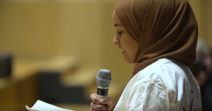 Screen shot of female young person talking on stage