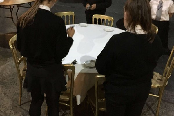 Young people setting table on a hospitality talent taster
